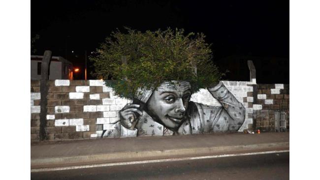 Street art: uomo disegnato con capelli di foglie
