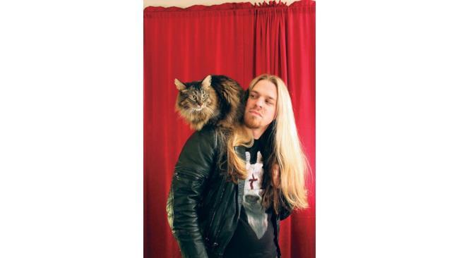 Un uomo con una chioma stupenda con un gatto dal pelo stupendo