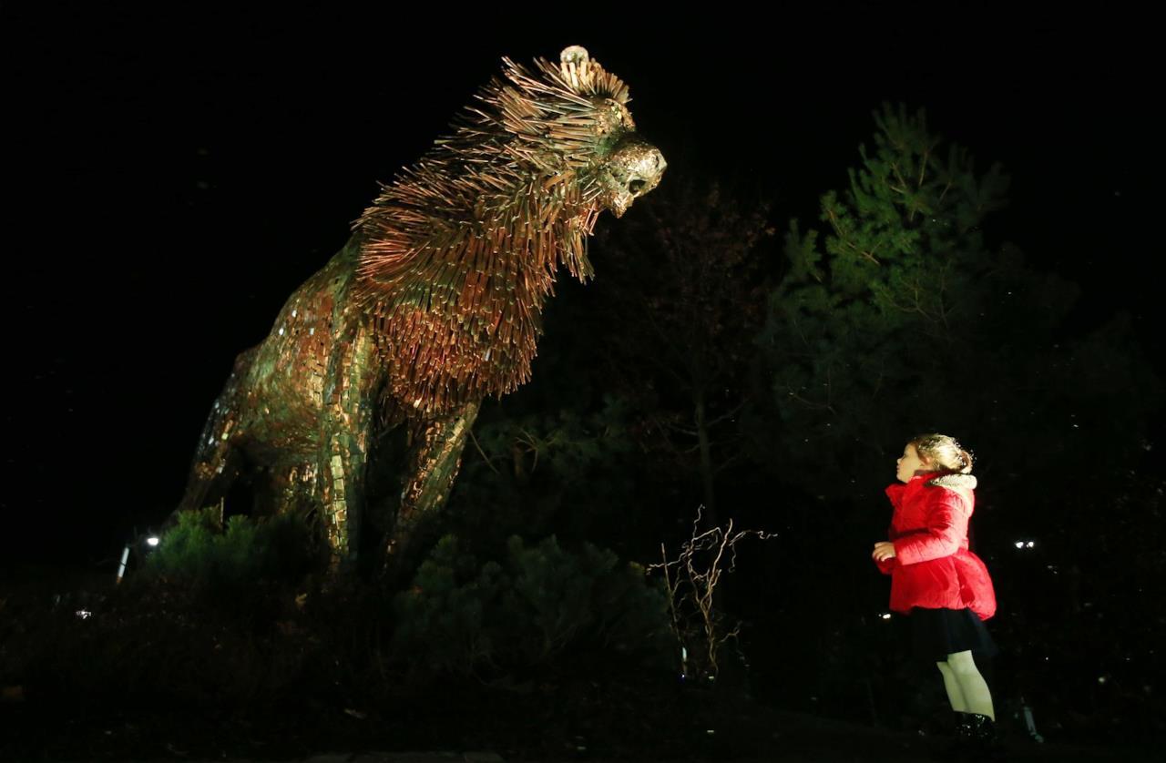 Una bamvina osserva la statua del leone Aslan