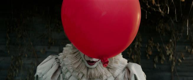 Il clown di IT nascosto dietro al palloncino rosso