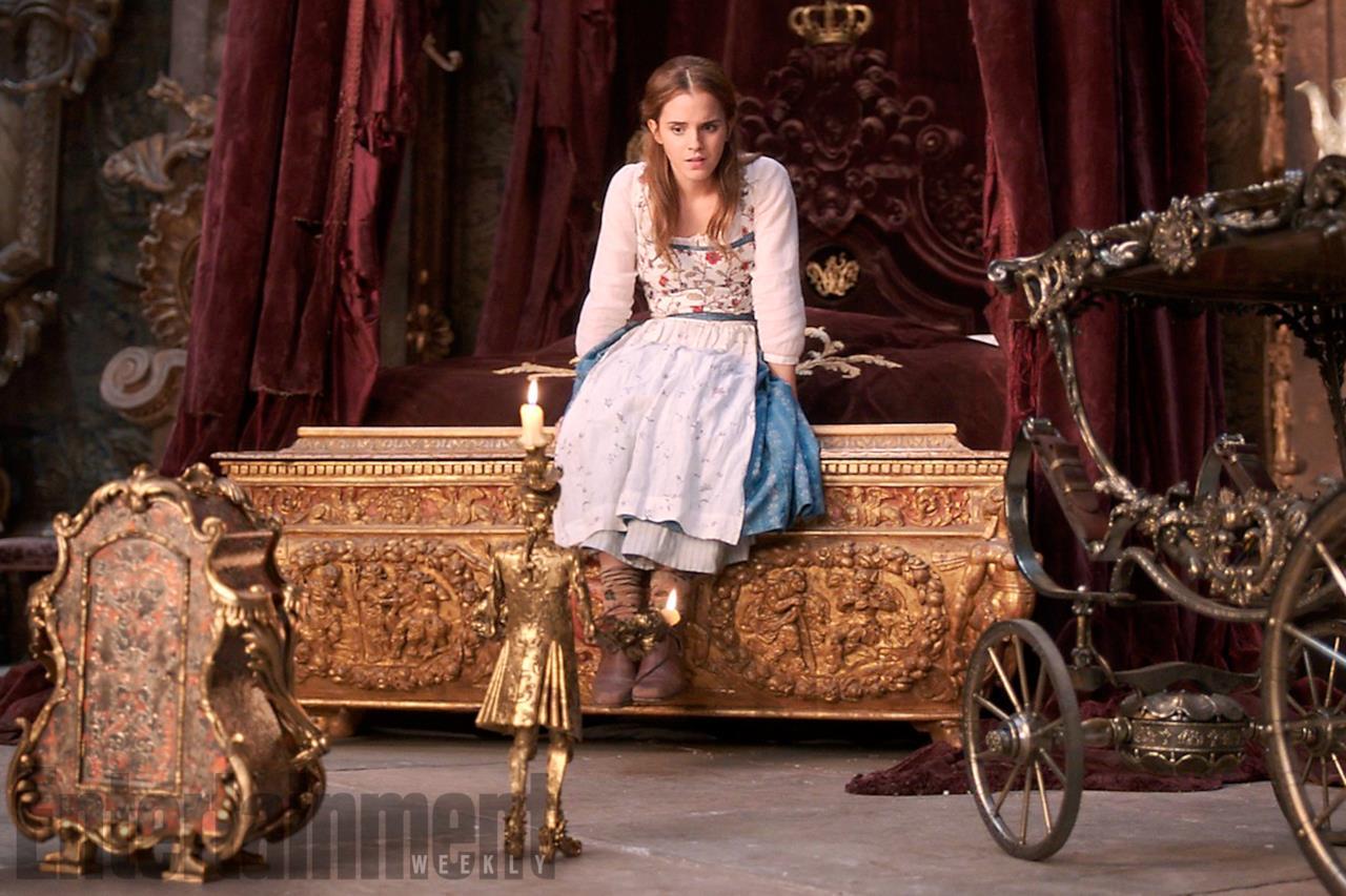 Belle siede sul letto mentre parla con Tockins e Lumière