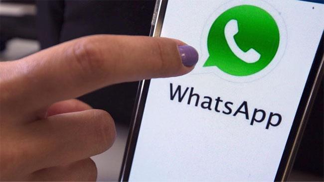 Dito che si appresta a lanciare WhatsApp sullo schermo di uno smartphone