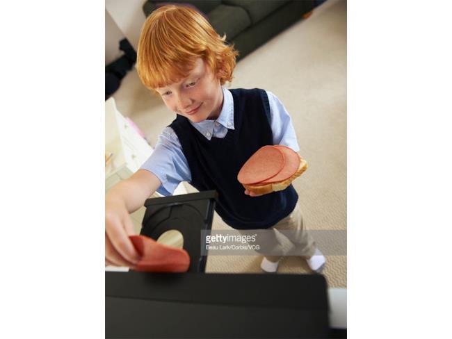 Un ragazzino con delle fette di un salume