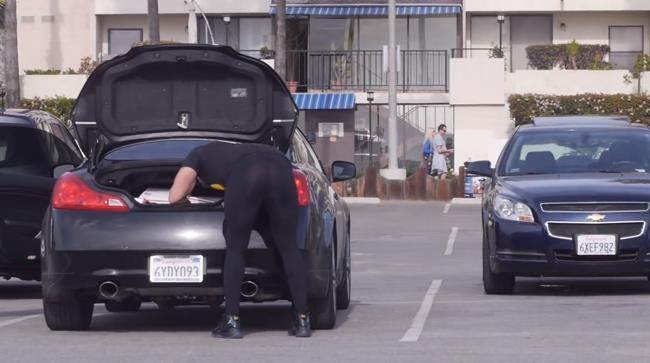Un uomo sistema delle borse nel baule della sua auto: scherzo dei leggins