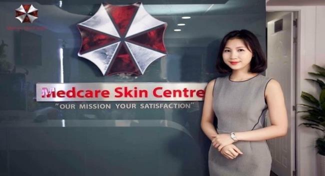 Una manager dell'azienda posa accanto al logo del centro estetico, simile a quello di Resident Evil.