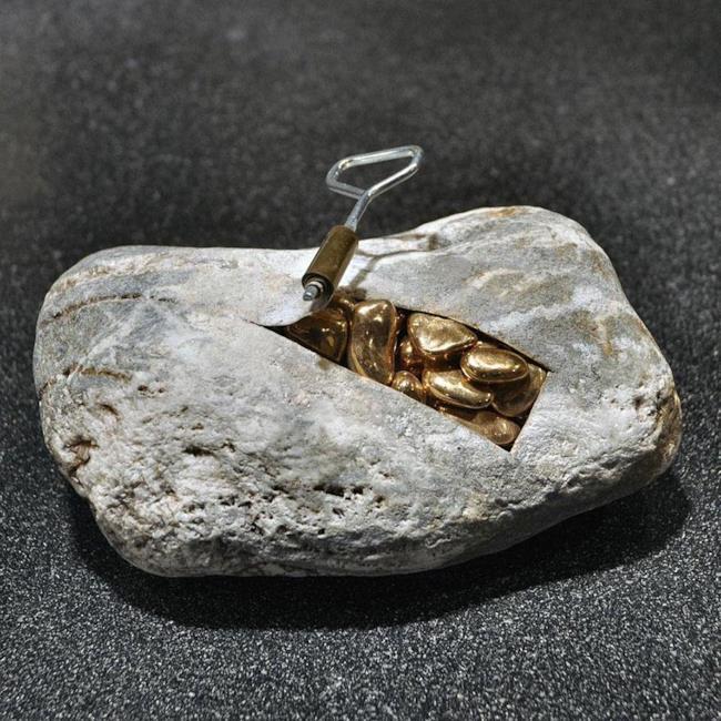 Scultura realistica: pietra con dei sassi dorati