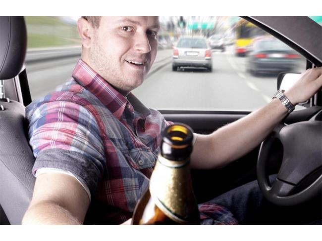 Un uomo guida con una birra