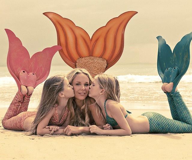 Una mamma con le figlie con ai piedi le pinne da sirena