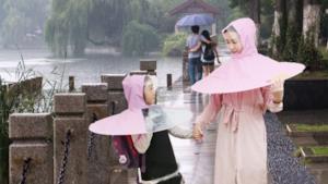 Madre e figlia si riparano dalla pioggia con un impermeabile a forma di ombrello