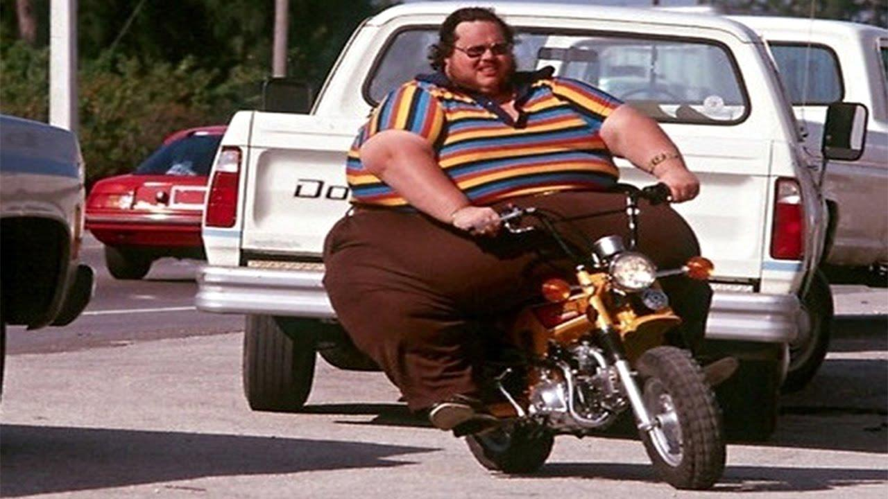 Un uomo molto grasso su una piccola moto