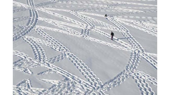 L'artista Simon Beck mentre cammina sulla neve
