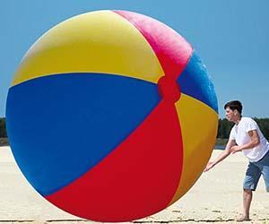 Un ragazzo accanto alla palla gigante da spiaggia