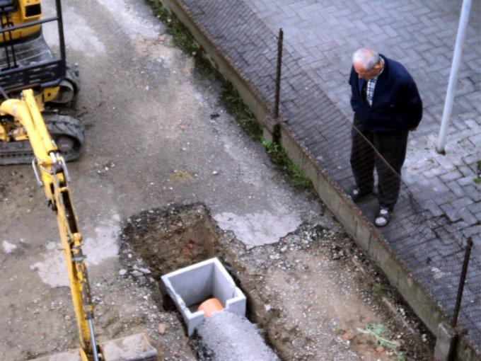 Un pensionato guarda attentamente i lavori in corso