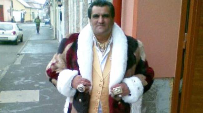 Un uomo vestito in modo troppo appariscente, ha anche una pelliccia stile reale