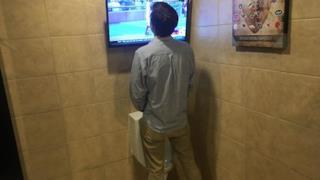 Un uomo intento a urinare mentre guarda la tv