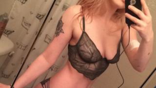 Selfie di una ragazza allo specchio in lingerie nera