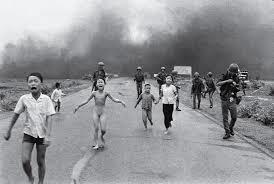 Una bambina nuda che scappa da un villaggio in fiamme
