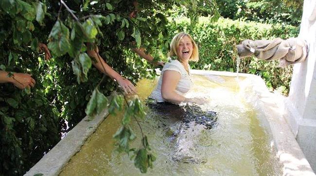 Uomo coperto di foglie getta donna in vasca