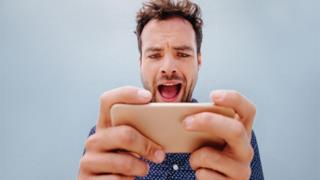 Un ragazzo guarda stupito il suo smartphone