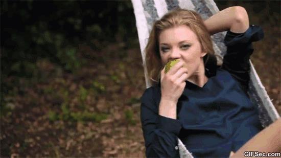 GIF donna si dondola su un'amaca e mangia una mela