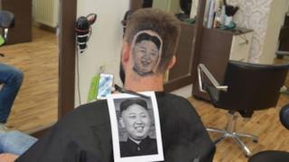 Kim Jong ritratto sulla testa di un cliente da un barbiere serbo