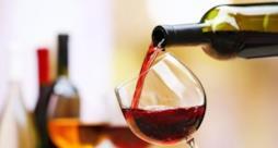 Una bottiglia da cui sgorga del vino rosso.