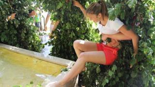 Svizzeri travestiti da arbusti che gettano donne nelle fontane