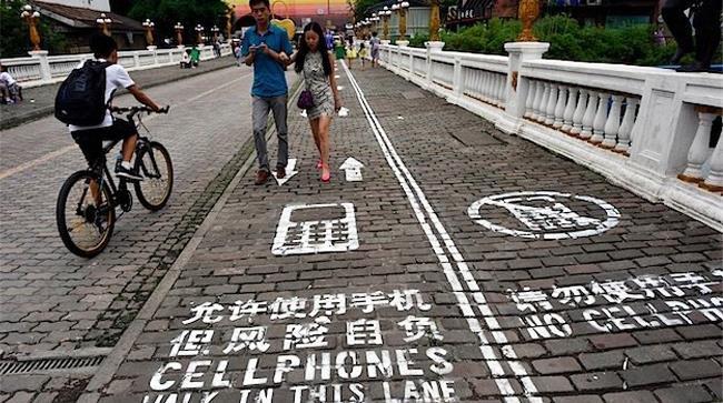 Corsia della strada dedicata ai pedoni che stanno usando il cellulari