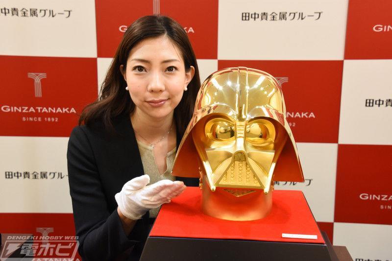 una ragazza vicino al casco d'oro di Darth Vader
