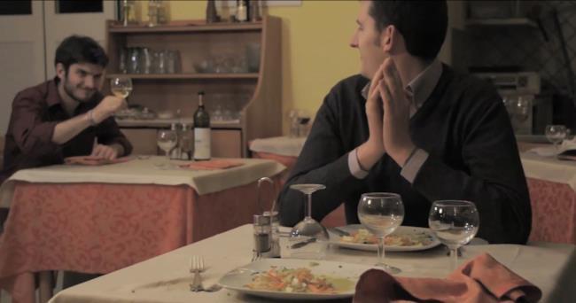 Un uomo ammicca ad un altro e alza il calice di vino per salutarlo nel video dei Minimad