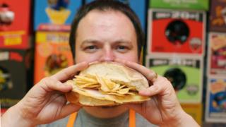 Andrew McMenamin con uno dei suoi panini farciti di patatine