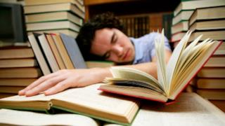 Uomo addormentato sui libri