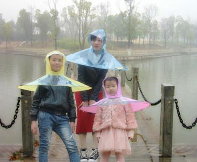 Alcuni ragazzi cinesi indossano degli impermeabili a forma di ombrello
