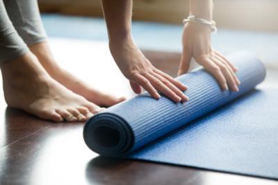 Una donna si appresta a esercitarsi sul tappetino da yoga