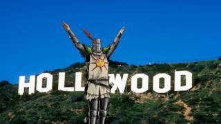 Il cavaliere Solaire di Astora saluta il sole davanti alla scritta di Hollywood