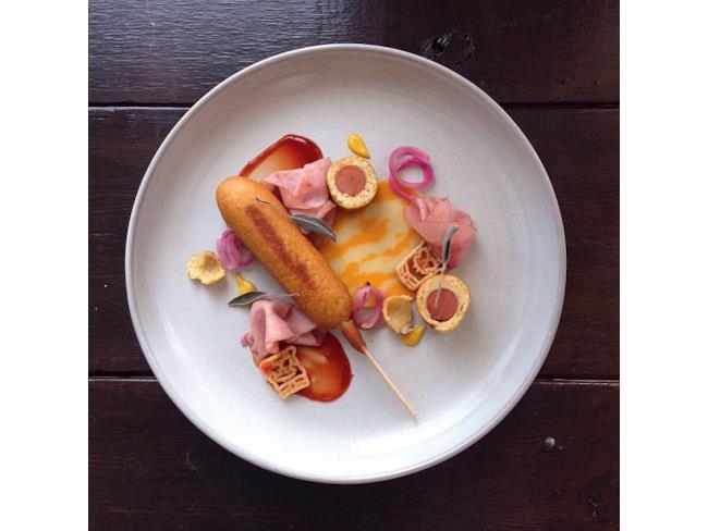 Wurstel condito con mostarda presentato come cibo d'autore