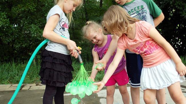 Bambini che riempono palloncini d'acqua con un'invenzione che ne può riempire 100 in meno di un minu