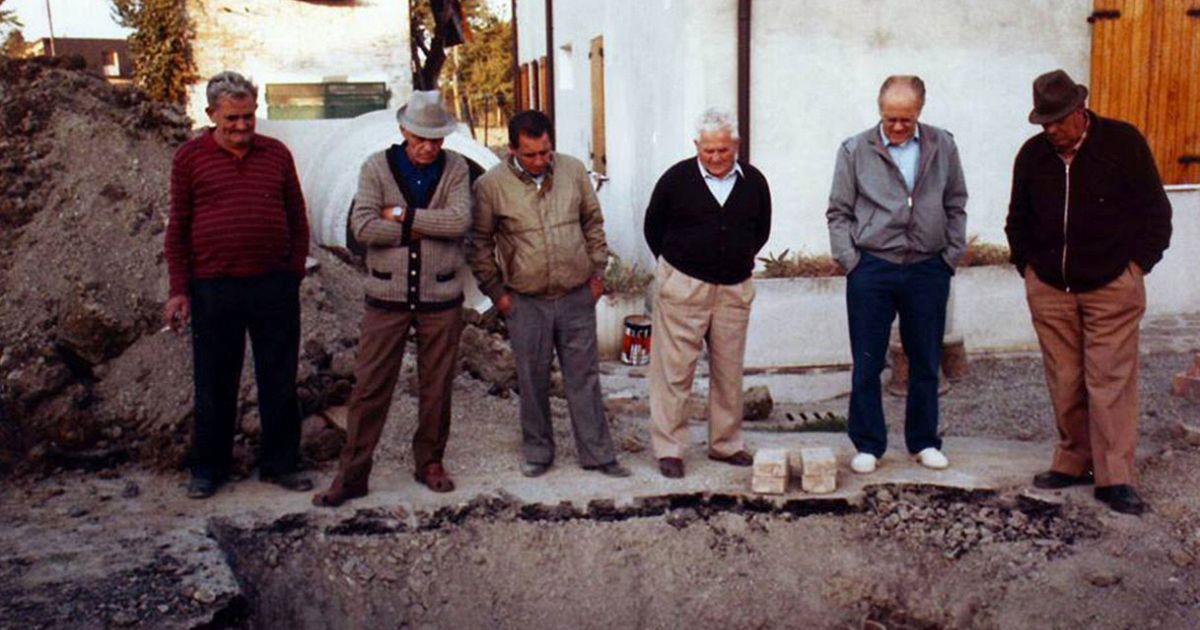 Un gruppo di anziani guarda un cantiere