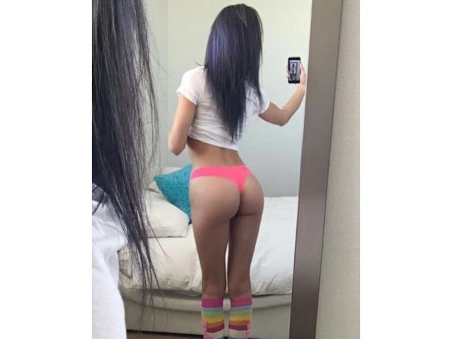 Selfie di una ragazza allo specchio in perizoma rosa