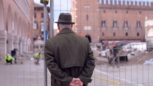 Un anziano intento a osservare un cantiere