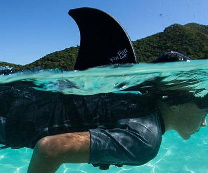 Un ragazzo nuota con la pinna da squalo