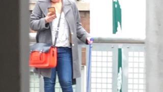 Una donna con una gallina al guinzaglio