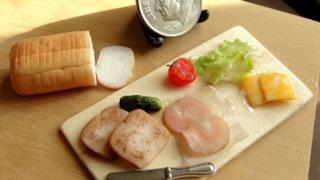 Un vassoio con pane, cetrioli, insalata, pomodori, formaggio e prosciutto