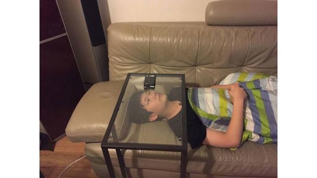 Ragazzo guarda un video sul telefono da sotto un tavolo di vetro