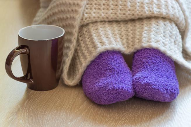 Piedi coperti da pesanti calzini e da una coperta di lana