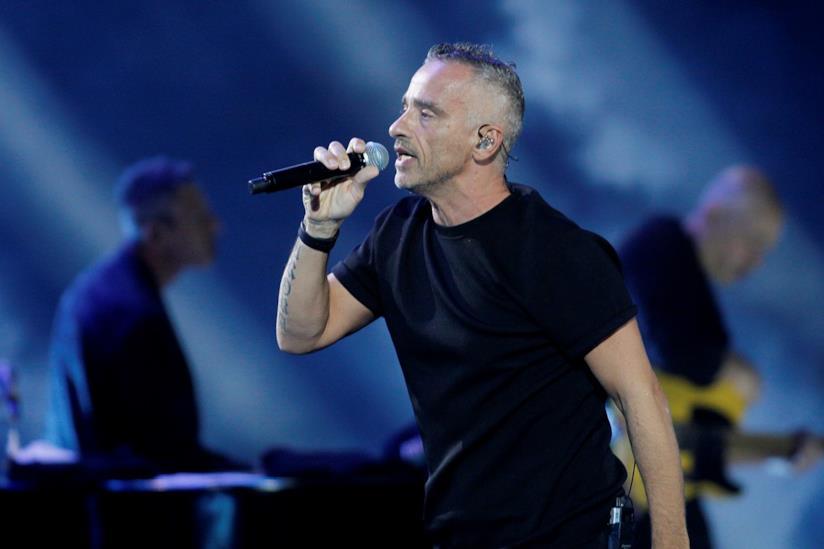 Eros Ramazzotti, in piedi, di profilo, con una t-shirt nera, canta al microfono