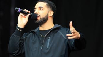 Drake, con una felpa nera, canta al microfono, in piedi