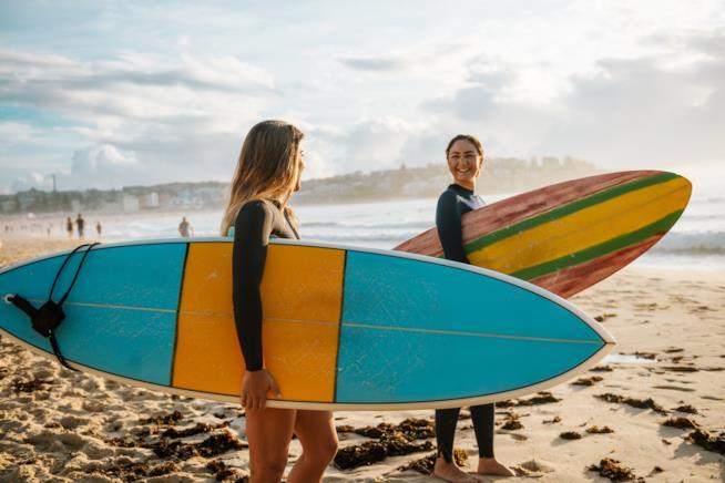 Due donne con la tavola da surf in mano.
