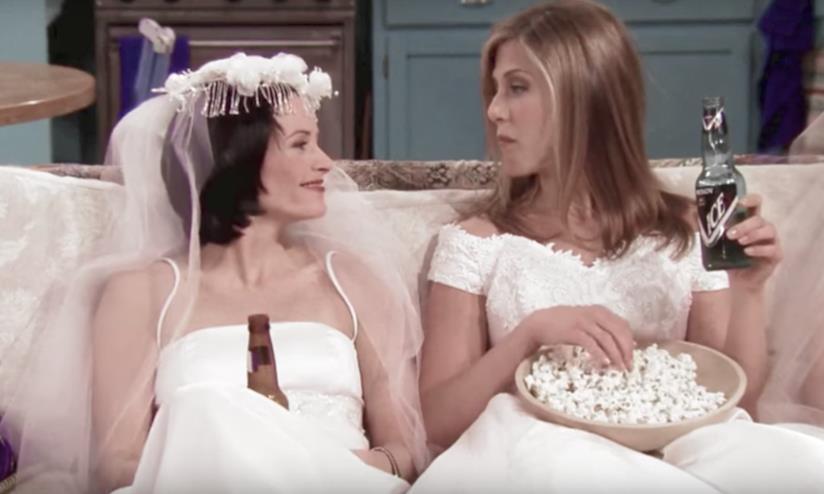 Monica e Rachel di Friends sedute sul  divano con birra e popcorn in abito da sposa