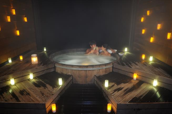Uomo e donna in una tinozza nella spa romantica